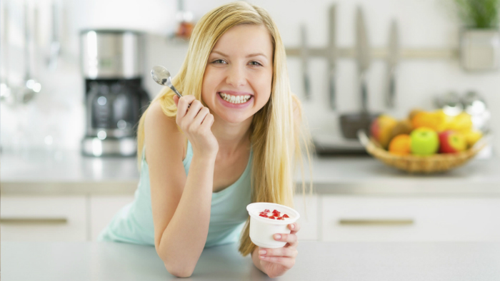 happy-young-woman-eating-yogurt-in-kitchen-design